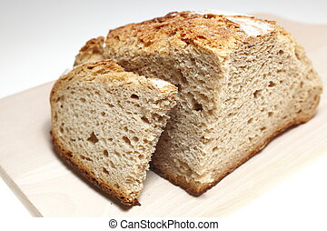 loaf bread - loaf brad with a wooden dish at background