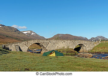 Tent by Spey river at Garva bridge, Scotland in spring -...
