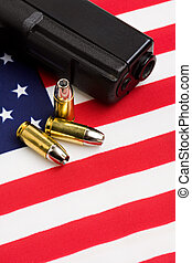 gun and bullets on flag - handgun and bullets closeup on...
