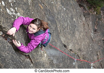 power girl - a smiling girl is climbing a rock
