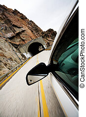 car approacting tunnel through mountains - car approaching...