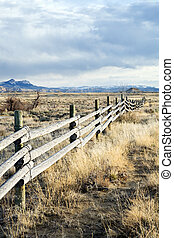 rural fence running through barren Wyoming landscape