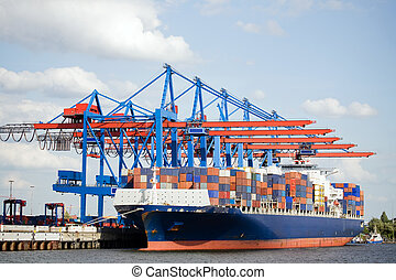 container ship in port terminal - huge freighter fully...