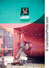 ship repairs in dry dock - rear view with screw propeller...