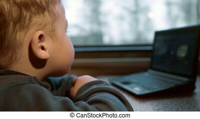 Little boy watching video on laptop in the train - Close-up...