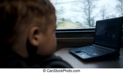 Boy watching movie or cartoon on laptop in the train -...