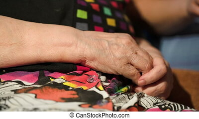 Young woman stroking her grandmothers hands - Dolly close-up...