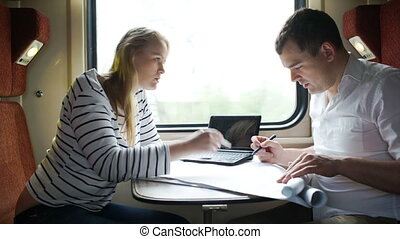 Man and woman discussing drawing during business trip in the...