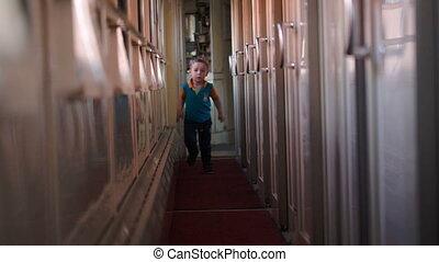 Happy boy running along the train hallway - Happy little boy...