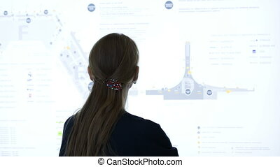 Woman exploring schematic map at the airport or trade cemter...