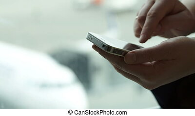 Close-up shot of female hands typing sms on smartphone -...