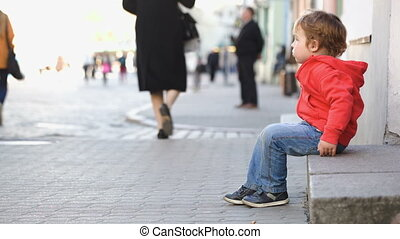 Little boy sitting alone in the street, people passing by