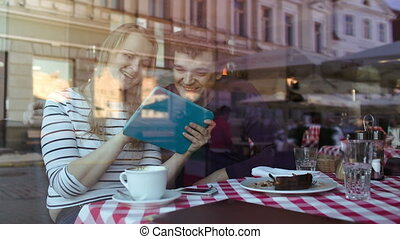 Happy young couple with tablet PC in a cafe