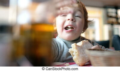 Cute boy eating a bun in a cafe - Close-up shot of a cute...