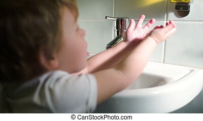 Boy washing hands with soft soap and turning off water -...