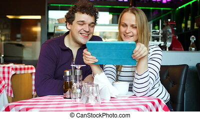 Young couple in cafe having a video chat on tablet PC