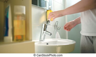Woman washing hands with liquid soap and then drying them with towel