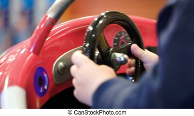 Child turning steering wheel of a toy car - Close-up shot of...