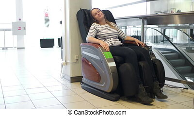 Woman relaxing in massage chair in trade center