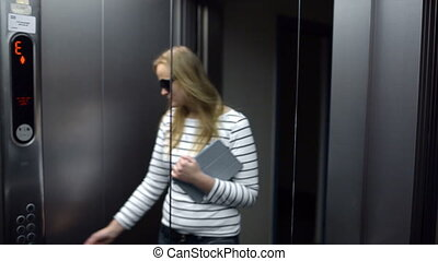 Young woman in the lift primping and make funny face - Young...