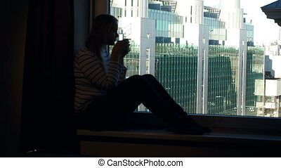 Woman drinking coffee on the windowsill with city view in...