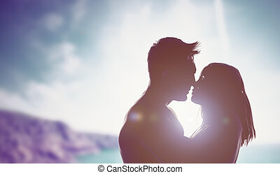 Loving couple backlit by a bright sun - Silhouettes of a...