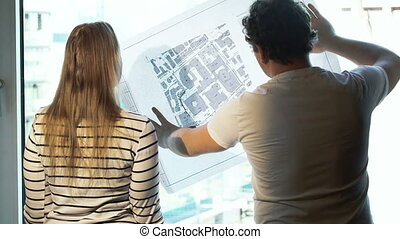 Two architects discussing a project looking at the city with...