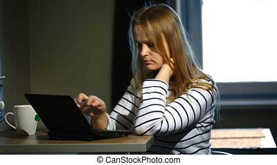 Woman working with laptop at home - Dolly shot of a young...