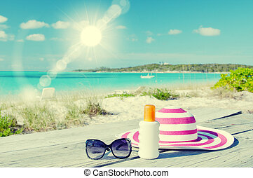 Sun lotion, sunglasses and hat