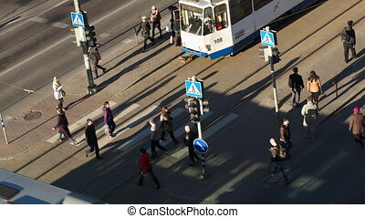 Pedestrians walking across the road in the city - Tilt and...
