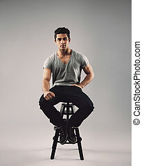 Smart young man sitting on stool - Portrait of smart young...