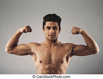 Muscular young man showing off his defined body - Portrait...