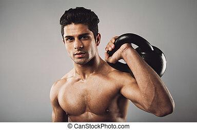 Hispanic fitness male model holding kettle bell - Portrait...