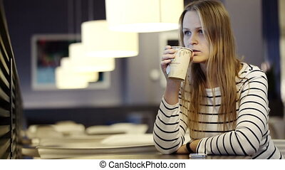 Woman in the cafe drinking tea and waiting for somebody -...