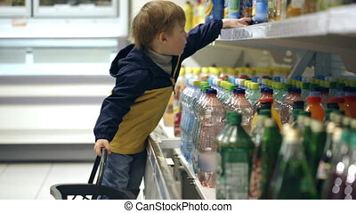 Little boy in the shop putting mineral water into the basket...