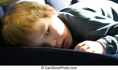 Little boy lying on the seat in the bus, car ot train