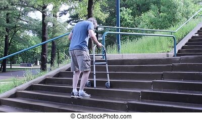 walker on stairs - mature man using a wheeled walker to...