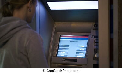Woman using ATM outdoor in the evening - Woman using outdoor...