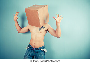 Young man with cardboard box on his head - A young man is...