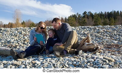 Family of three sitting on the stony shore and watching something pad