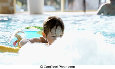 Little boy swimming in the pool with rubber ring - Little...