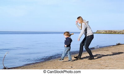 Mother and son throwing wooden pieces into the water -...