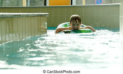 Boy with rubber ring swimming in water labyrinth - Happy...