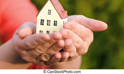 Couple holding a small toy house in hands - Male hands...