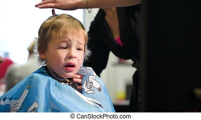 Boy taking off the cape while during haircut - Boy unwilling...