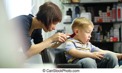 Little boy during haircut at the hairdressing saloon