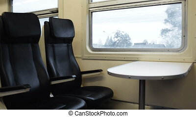 Two empty seats with table in the moving train - Two empty...