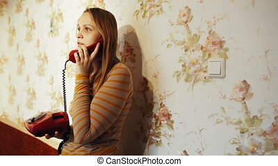 Young woman talking on the phone at home