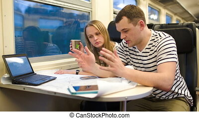 Young people working with plan in the train - Young man and...