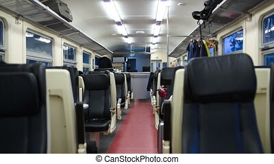 Empty carriage of moving train with gangway and two rows of...